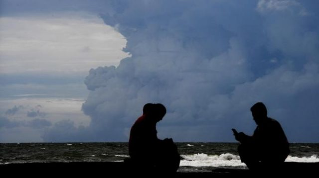 Warga beraktivitas dengan latar belakang awan panas semburan Gunung Anak Krakatau terlihat dari kawasan Carita,