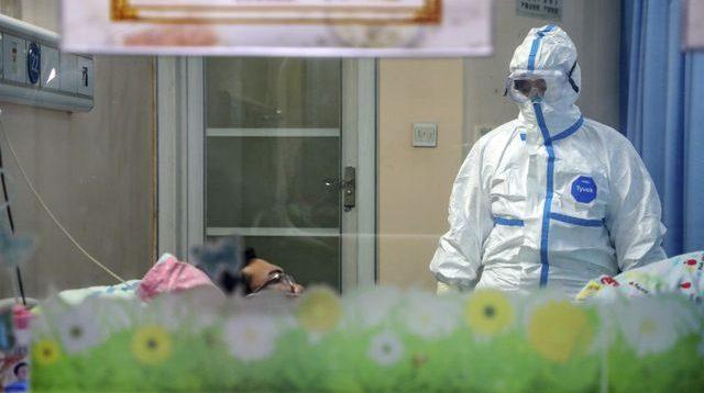 Seorang dokter mengenakan pakaian pelindung merawat warga yang terkena virus corona. (Foto: Chinatopix via AP/Kumparan.com)